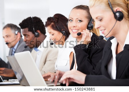 Happy Co-workers Wearing Headsets Working In Call Center