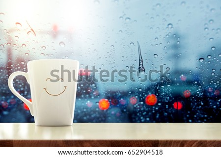 Happy Coffee Mug with smiley face on desk inside glass window, Blurred traffic jam light in city as outside view, Relaxing in cafe or Rest on rainy day