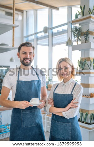Happy coffee shop owner couple standing inside their shop. Man and woman baristas standing inside their cafe wearing apron with the man holding coffee cup #1379595953
