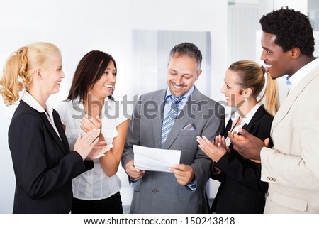 Happy Colleagues Applauding Businessman Holding Paper In Office
