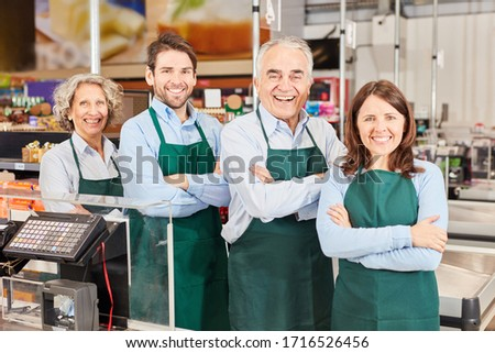 Happy colleagues as sales team with market leader at checkout in supermarket