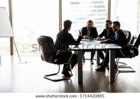 Happy colleagues having fun at meeting in boardroom, sitting at table together, sharing ideas, discussing project strategy, smiling satisfied hr managers listening to successful job candidate