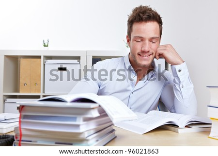 Happy college student learning with books at desk for exams