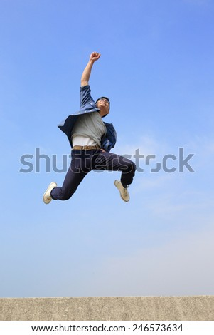 Happy College student man run and jump with blue sky background full length asian male