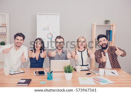 Shutterstock Happy collegues successfuly ending project and showing thumbs up.