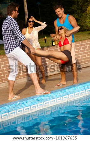 Happy companionship having fun at summertime by swimming pool.