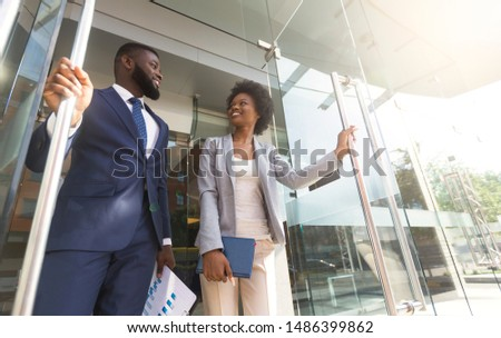 Happy confident african american business people walking out of modern office center after successful meeting. Low-Angle shot with copy space