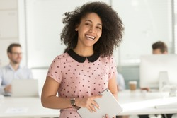 Happy confident african american business woman employee holding digital tablet looking at camera standing in office, smiling millennial mixed race female intern manager young professional portrait