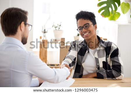 Happy confident african applicant shaking hand of hr manager offer new job, black candidate getting hired at job interview, handshake client at meeting, making good first impression employment concept