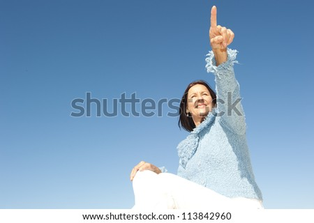 Happy confident and focused mature woman pointing with finger, isolated with blue sky as background and copy space.