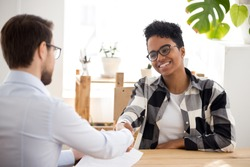 Happy confident applicant of African descent shaking the hand of an HR manager offering a new job. A black candidate getting hired at job interview/handshaking with client at meeting/making a good first impression. Employment concept