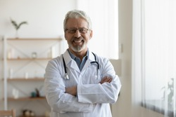 Happy confident bearded old professional doctor standing arms crossed looking at camera. Smiling senior adult physician, reliable successful therapist wearing white lab coat and stethoscope, portrait.