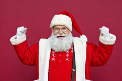 Happy confident cool old bearded Santa Claus winner raising fists celebrating triumph, success, or showing muscles advertising gym Merry Christmas sale discount concept isolated on red background.