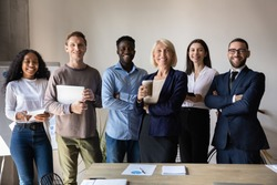 Happy confident diverse old and young business people stand together in office, smiling multiethnic professional colleagues staff group look at camera, human resource concept, team corporate portrait