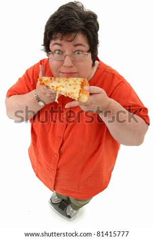 Happy confident obese forty-five year old woman on scale with slice of cheese pizza over white.