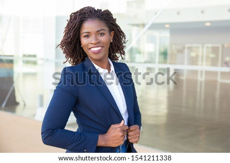 Happy confident professional posing near office building. Young African American business woman standing outside, adjusting formal jacket, looking at camera, smiling. Successful businesswoman concept
