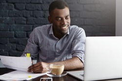 Happy confident young African-American businessman in formal wear filling in papers while managing finances at cafe during lunch break, sitting at table in front of open laptop, having cappuccino