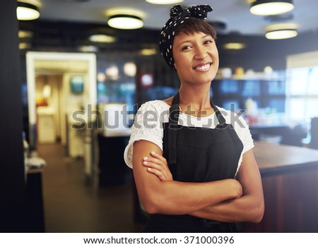 Happy confident young African American small business owner standing in her shop with folded arms smiling at the camera