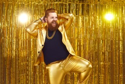 Happy confident young man with ginger beard and mustache wearing funny golden suit with bling gold chain necklace performing on stage at night club disco party, dancing, singing songs and having fun