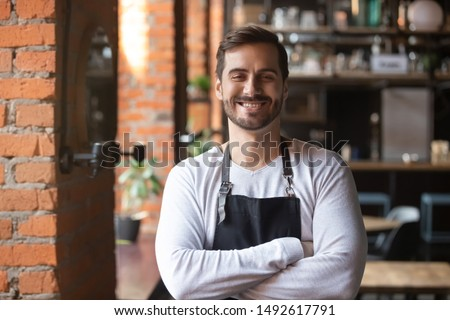 Happy confident young waiter entrepreneur looking at camera, smiling male small cafe business owner employee standing in restaurant, millennial businessman wear apron posing in coffee shop portrait
