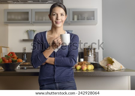 Happy contented housewife in her kitchen giving the camera a warm friendly smile as she relaxes with a mug of coffee with fresh fruit on the counter behind her