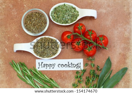 Happy cooking card with cherry tomatoes, fresh and dried herbs on terracotta surface