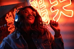 Happy cool fashion funky African young black hipster lady wears trendy glasses headphones listening dance pop dj music standing in neon night club light at style party. Translation: Chicken laugh