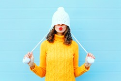 Happy cool girl blowing red lips makes air kiss wearing a knitted hat, yellow sweater over blue background
