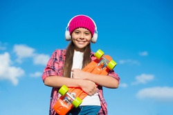 Happy cool penny board skater listen to music playing in headphones sunny sky outdoors, adventure.