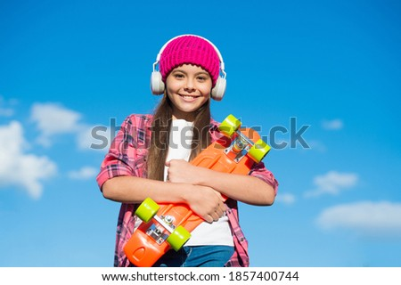 Happy cool penny board skater listen to music playing in headphones sunny sky outdoors, adventure. Zdjęcia stock ©