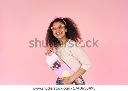 Photo of Happy cool smiling young african american teen gen z girl skater wearing sunglasses holding skateboard looking at camera posing with skate in hands isolated on pink studio background, portrait.