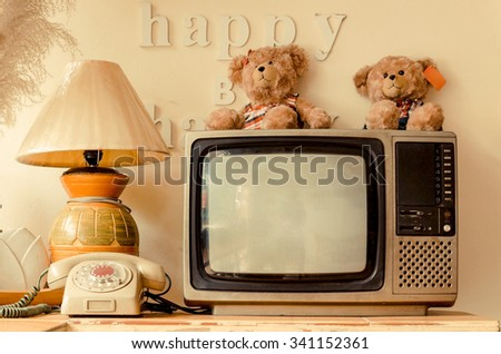 happy corner of a house with decoration of words saying think happy be happy, bear dolls, old telephone, vase, pot, lamp, plant, bird feather, basket, television
