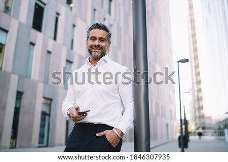 Happy corporate director in formal white shirt holding cellphone gadget in hand and smiling at camera, half length portrait of successful middle aged employee with smartphone posing in downtown Stock fotó ©
