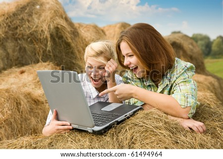 Happy country girls relaxing with laptop in farm