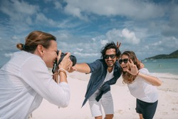 Happy couple and photographer on a tropical beach. Photoshoot with a professional photographer on a background of white sand, sea and cloudy sky. Newlyweds are photographed on a honeymoon at a resort