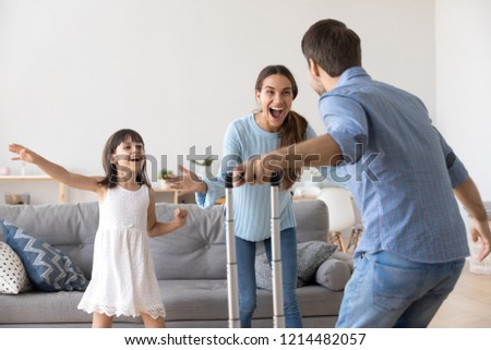 Happy couple and small daughter standing in living room at home. Cheerful wife little girl meets husband father he arrived at home with suitcase luggage from long business trip. Family reunion concept