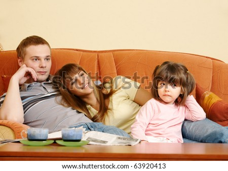 Happy couple and their daughter relaxing on sofa and watching TV - stock photo