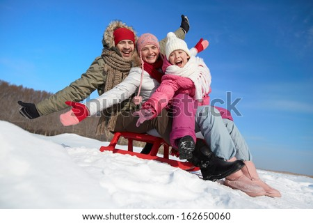 Happy couple and their daughter sitting on sledge