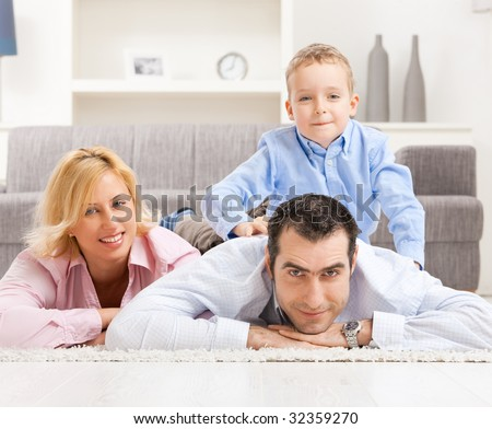 Happy couple and their son lying together on carpet in living room.