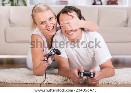 Happy couple are spending time together. Playing computer game.