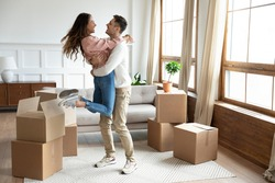 Happy couple arrive at bought house, cheerful husband lifts up on hands beloved wife family begin new life at first dwelling. Loan and mortgage, bank lending, delivered goods satisfied clients concept