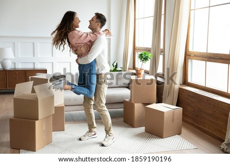 Happy couple arrive at bought house, cheerful husband lifts up on hands beloved wife family begin new life at first dwelling. Loan and mortgage, bank lending, delivered goods satisfied clients concept Stockfoto ©
