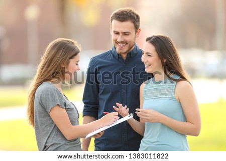 Happy couple asking a survey standing in the street
