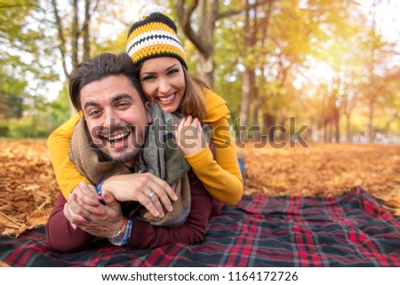 Happy couple at a park in autumn smiling at the camera