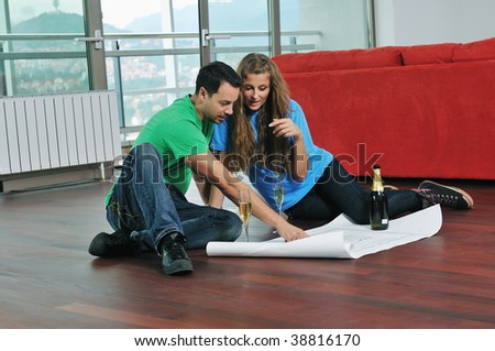 happy couple at big bright comfort apartment celebrate with glasses of champagne and looking and planing with blueprints papers