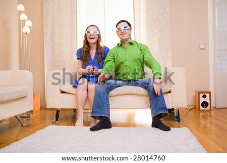 Happy couple at home watching movie in 3D glasses.