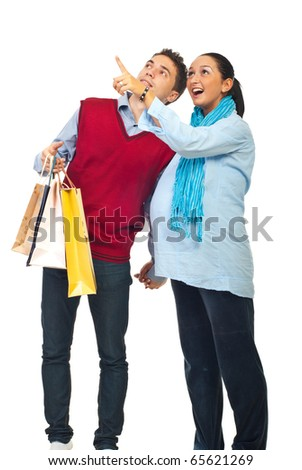 Happy couple at shopping ,pregnant wife showing something to her husband and pointing up isolated on white background