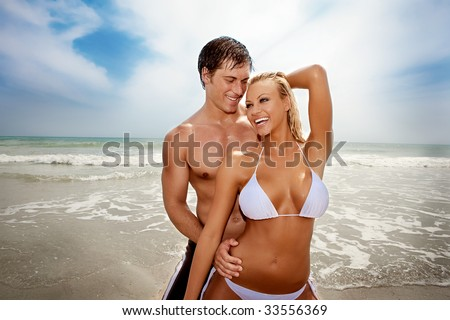 Happy couple at the beach, both wearing swimsuits.