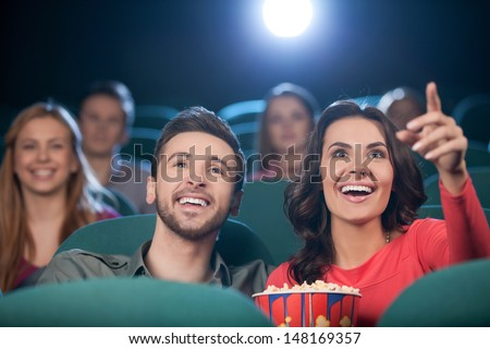 Happy couple at the cinema. Cheerful young couple watching movie at the cinema