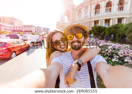 Happy couple, attractive woman and man walking  in city and  enjoying romance. Lovers making selfie, smiling and have fun together. Odessa, Ukraine.